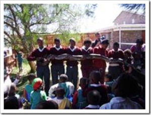 Young school children entertained by the snake man during the Jonga refraction day camp